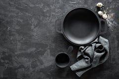Pusta żeliwna niecka z cutlery na ciemnym tle dla restauracyjnego menu Obrazy Royalty Free