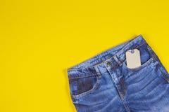 Pusta etykietki metki etykietka z niebieskimi dżinsami na żółtym tle zdjęcie royalty free