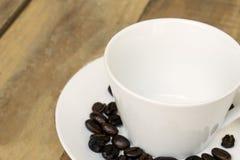 Pusta filiżanka z kawowymi fasolami na spodeczku zdjęcie royalty free