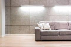 Pusta kanapa przeciw iluminującej ścianie w mieszkaniu zdjęcie royalty free