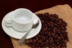 Pusta kawy espresso filiżanka na piec kawowych fasolach na burlap torbie obrazy stock