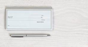 Pusta książeczka czekowa i srebny pióro na białym desktop Fotografia Stock