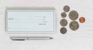 Pusta książeczka czekowa z piórem i monety na białym desktop Zdjęcia Stock