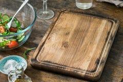 Pusta kuchni deska z pucharem sałatka na drewnianym stole obraz stock