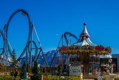 Pusta linia kolejowa ostro protestować z carousel w parku rozrywki z jasnym obraz royalty free