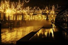 Pusta nocy restauracja, udział stoły i krzesła bez jeden, magiczni czarodziejscy światła na drzewach lubimy bożego narodzenia świ Fotografia Stock