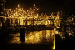 Pusta nocy restauracja, udział stoły i krzesła bez jeden, magiczni czarodziejscy światła na drzewach lubimy bożego narodzenia świ Obraz Royalty Free