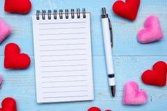 Pusta nutowa książka i pióro z kierową kształt dekoracją na błękitnym drewnianym stołowym tle czerwieni i menchii Miłość, ślub, R fotografia stock
