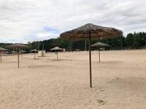 Pusta opustoszała plaża w złej pogodzie, zimna jesień w martwym sezonie z pokrywającymi strzechą słońce parasolami przeciw niebie obrazy stock