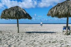 Pusta plaża, dwa plażowego parasola, bryczki longue postać mężczyzna chodzi morze, ślada ludzie w piasku, fotografia royalty free