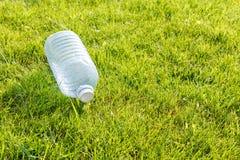 Pusta plastikowa butelka na zielonym gazonie Poj?cie: zanieczyszczenie ?rodowiska obrazy stock