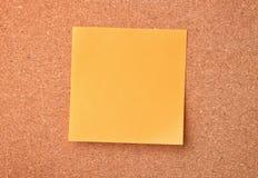 Pusta pomarańczowa kleista notatka na korek desce Zdjęcie Stock