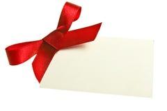Pusta prezent etykietka wiązał z łękiem czerwony atłasowy faborek. Odizolowywający na bielu, z miękkim cieniem Zdjęcia Royalty Free
