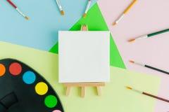 Pusta sztuki kanwa na sztaludze z stubarwnymi farb muśnięciami i sztuki paletą na pastelowym tle Fotografia Stock