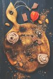 Pusta tnąca deska dekorował z słodka bułeczka z czekoladową śmietanką, migdałami i czekolada kawałkami, Wieśniaka styl Kremowi sł obraz royalty free