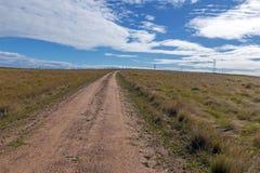 Pusta Wiejska droga gruntowa Prowadzi Przez Suchego zima obszaru trawiastego Zdjęcie Royalty Free