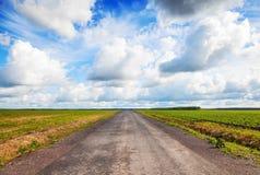 Pusta wiejskiej drogi perspektywa z chmurnym niebem Fotografia Royalty Free