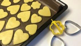 Puste ciasteczka z ciasteczkami leżą na kartce do pieczenia O różnych kształtach Obok drewnianego wałka i form do wyciskania cias zbiory