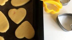 Puste ciasteczka z ciasteczkami leżą na kartce do pieczenia Obok drewnianego wałka i form do wytłaczania kawałków ciasta zbiory
