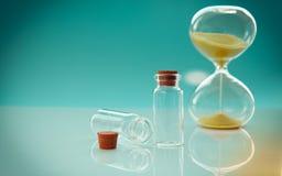 Puste małe butelki z korkowym stopper i hourglass na stonowanym tle, w górę zdjęcia royalty free