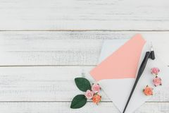Puste miejsce menchii karta w białej kopercie dekoruje z menchii róży papierowym kwiatem Obrazy Stock