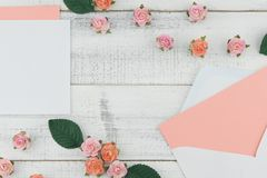 Puste miejsce menchii karta w białej kopercie dekoruje z menchii róży papierowymi kwiatami Zdjęcie Royalty Free