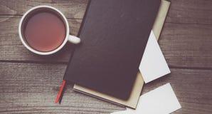 Puste wizytówki z piórem, notatnikiem i herbacianą filiżanką na drewnianym biuro stole, Zdjęcia Stock