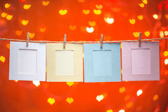 Pustego papieru rama fotografie wiesza na clothesline nad kierowym bokeh błyskotania tłem Zdjęcie Royalty Free