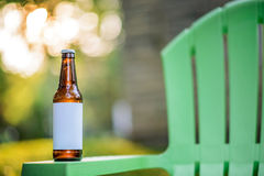 Pustej etykietki Piwna butelka na Zielonym krześle ogrodowym Obraz Stock