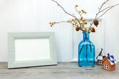 Pustej fotografii ramowa i błękitna waza z wysuszonymi kwiatami na drewnianym bac Obraz Stock
