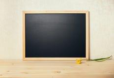 Pustej puste miejsce szkoły czerni nowa deska z tulipanem na stole, zamyka up Fotografia Stock