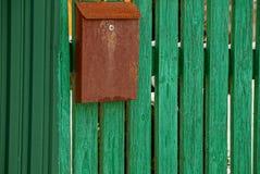 Pusty变褐在绿色木篱芭的邮箱 图库摄影