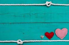Pusty błękitny drewno znak z czerwonymi sercami i kędziorek białą arkaną graniczymy z kępkami Zdjęcia Royalty Free