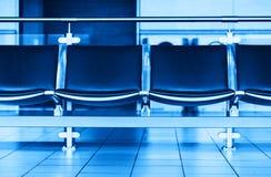 Pusty błękitny lotniskowy siedzenie ławki bokeh tło Fotografia Royalty Free
