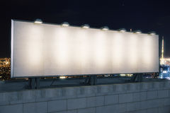 Pusty biały billboard na wierzchołku budynek przy nocy miasta backg Fotografia Stock