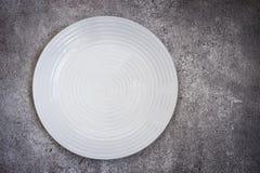 Pusty biały ceramiczny talerz Na betonowym tle Odgórnego widoku dowcip obraz royalty free