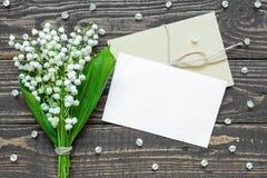 Pusty biały kartka z pozdrowieniami i koperta z białą lelują dolina kwitniemy Obraz Stock