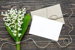 Pusty biały kartka z pozdrowieniami i koperta z białą lelują dolina kwitniemy Obrazy Stock