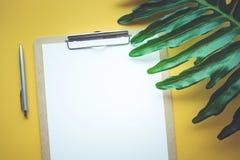 Pusty biały notepaper z tropikalnymi liśćmi kłaść na kolorze żółtym Zdjęcie Royalty Free