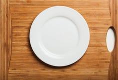 Pusty bielu talerz na drewnianej desce Zdjęcia Stock