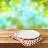 Pusty bielu talerz na drewnianym stole nad zamazaną bokeh naturą Zdjęcie Stock