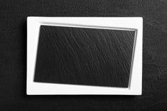 Pusty bielu talerz z czerń kamienia powierzchnią zdjęcie stock