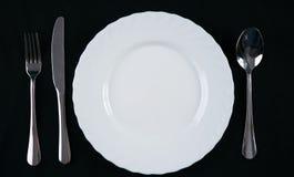 Pusty bielu talerz z srebnym rozwidleniem, nożem i łyżką odizolowywającymi na czarnym tle, Miejsca obiadowy położenie Odgórny wid Zdjęcie Stock