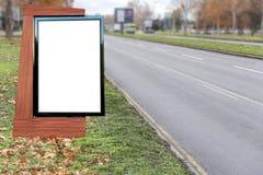 Pusty billboard na miasto asfaltowej drodze na czystym dniu z udziałem drzewa obraz stock