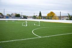 Pusty boisko do piłki nożnej z zieloną trawą i obalający brama Obraz Royalty Free