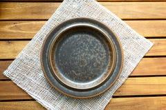 Pusty brązu talerz na drewnianym stołowym widoku od above zdjęcia stock