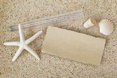 Pusty brown papier na zewnątrz tubki z korkowym deklem usuwał na piasku Zdjęcia Stock