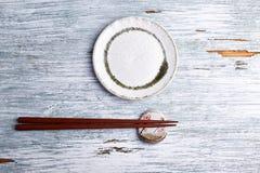 Pusty ceramika talerz, drewniani chopsticks i chopstick, odpoczywamy na nieociosanym drewnianym tle zdjęcia royalty free