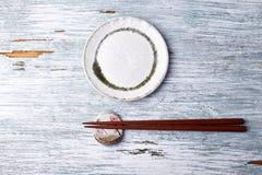 Pusty ceramika talerz, drewniani chopsticks i chopstick, odpoczywamy na nieociosanym drewnianym tle obrazy royalty free