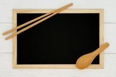 Pusty chalkboard z drewnianą łyżką i chopstick na białym drewnianym deski tle obraz stock